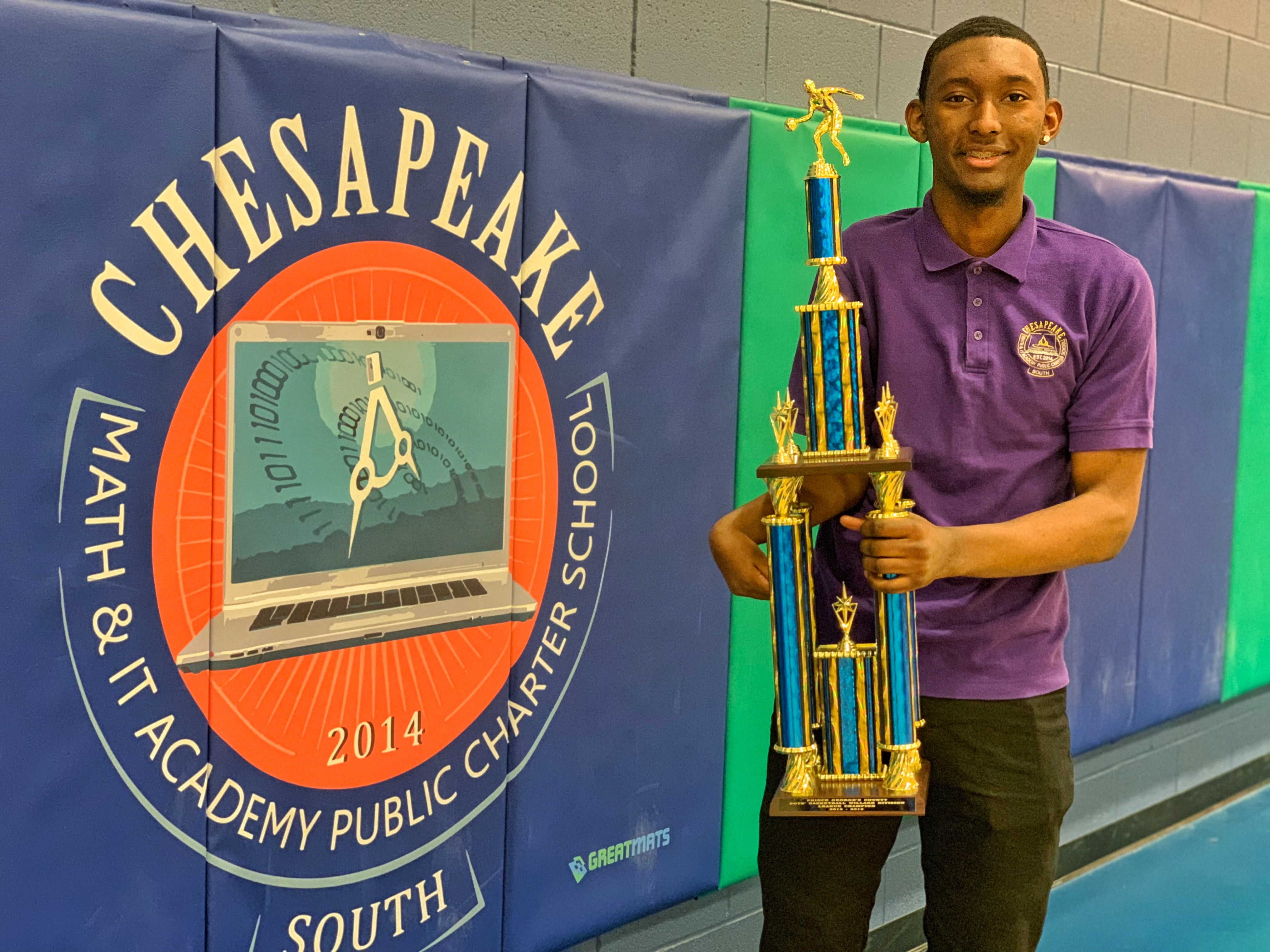 CMIT South basketball player Kennedy Watkins holds the school's first county division championship trophy.